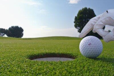 Fototapet en man som driva en boll i en golf hål