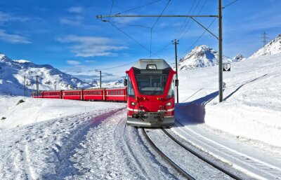 Fototapet En röd schweizisk tåg kör genom snön