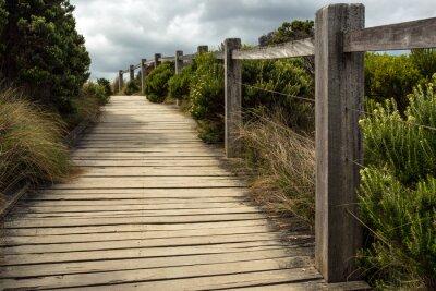 Fototapet En trä gångväg längs ett staket med grön växtlighet som växer på båda sidor under en molnig himmel. Detta ligger någonstans längs Great Ocean Road i Australien.