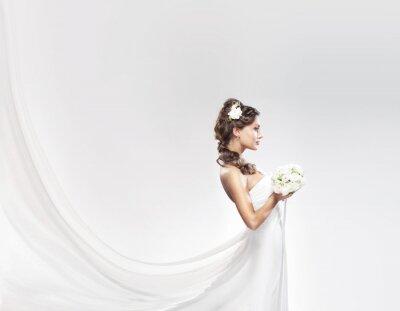 Fototapet En ung kaukasiska brud poserar i en vit klänning med blommor