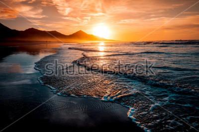 Fototapet Fantastisk strand solnedgång med oändlig horisont och ensamma figurer i fjärran, och otroliga skummande vågor. Vulkaniska kullar i bakgrunden i idylliska varma färger.