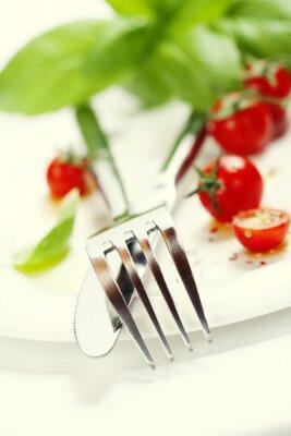 Fototapet färska tomater, kniv och gaffel på en tallrik