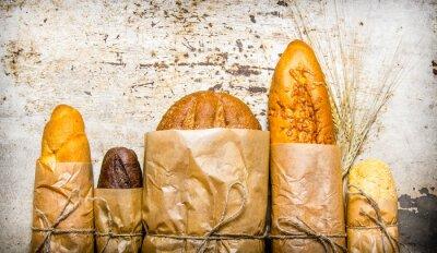 Fototapet Färskt bröd inslagna i papper. På rustik bakgrund.