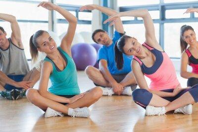 Fototapet Fitness klass och instruktör sittande och stretching händer