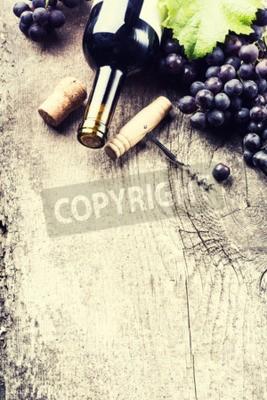 Fototapet Flaska mörkt vin, druva och korkar på gammalt trä bakgrund