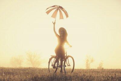 Fototapet Flicka med paraply på en cykel på landsbygden i soluppgången tid