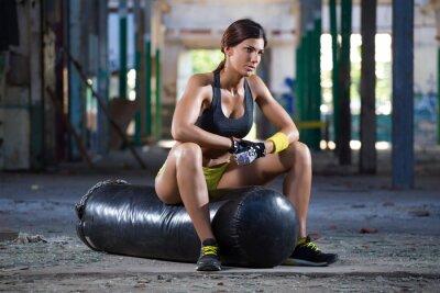 Fototapet flicka sittplatser på boxning väska