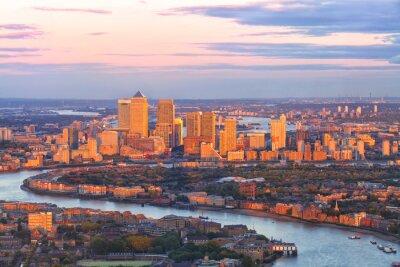 Fototapet Flygfoto över östra London finansiella distriktet i Canary Wharf Docklands inringat av Thames, med byggnader upplysta av färgrik solnedgång