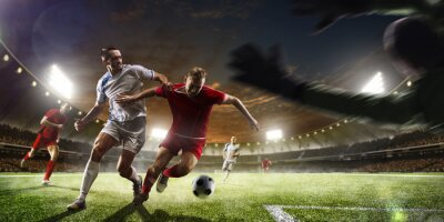 Fototapet Fotbollsspelare i aktion på solnedgången stadion bakgrund panorama
