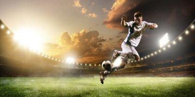 Fototapet Fotbollsspelare i aktion på solnedgången stadion panorama bakgrund