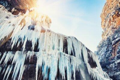 Fototapet Fryst vattenfall i bergen i solnedgången.