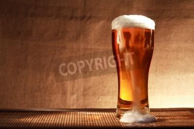 Fototapet Full glas friskhet öl med skum på bordet mot grå duk bakgrund
