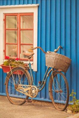 Fototapet Gammal rostig dam cykel framför ett svenskt hus
