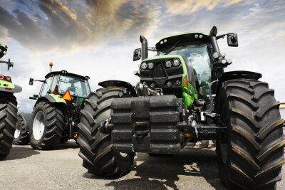 Fototapet gigantiska traktorer som mot en solnedgång himmel och moln