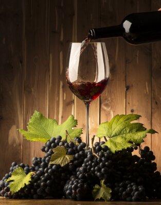 Fototapet Glas med rött vin och grapeson träbordet