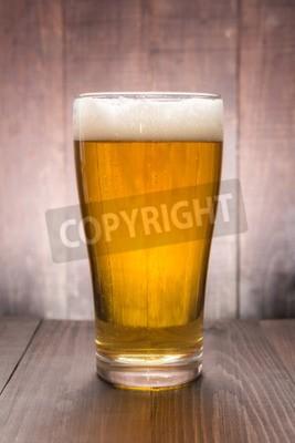 Fototapet Glas öl på trä bakgrund.