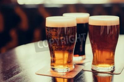 Fototapet Glasögon av ljus och mörk öl på en pub bakgrund.