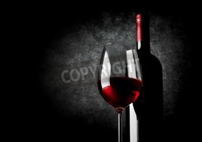 Fototapet Glassen rött vin på en svart bakgrund