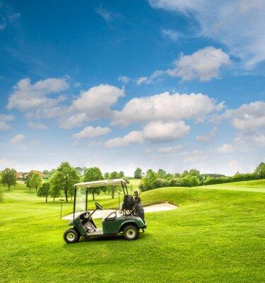 Fototapet Golfbil på en golfbana. Grönt fält och molnig blå himmel