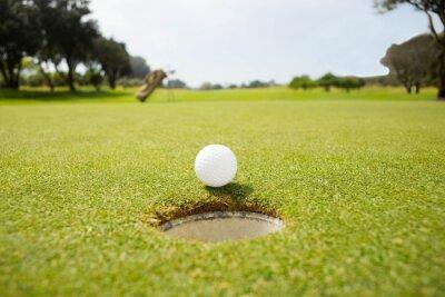 Fototapet Golfboll vid kanten av hålet