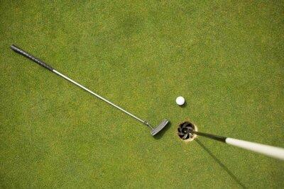 Fototapet Golfklubba och golfboll på green bredvid flagga
