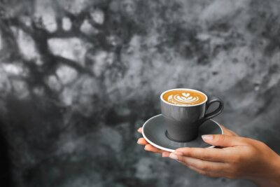 Fototapet Gray cup of fresh cappuccino in woman hands on background of gray concrete cement textured wall. Trendy hipster cafe design.