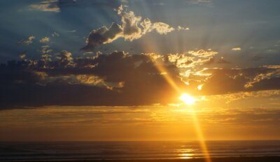 Fototapet Grumlig solnedgången över havet med Sunbeams in the Sky
