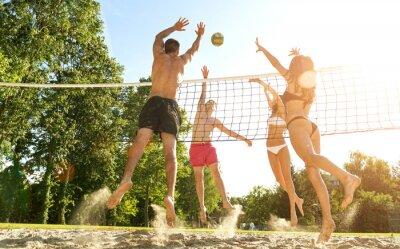Fototapet Grupp unga vänner spela volleyboll på stranden