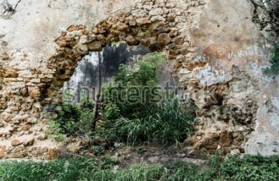 Fototapet Hål i väggen av övergiven stenbyggnad.