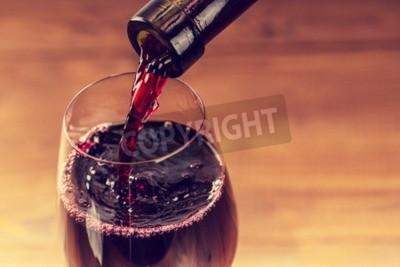 Fototapet Hällande rött vin i glaset mot trä bakgrund