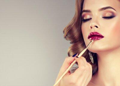 Fototapet Hand make-up mästare, målning läppar ung vacker modell. Makeup pågår.