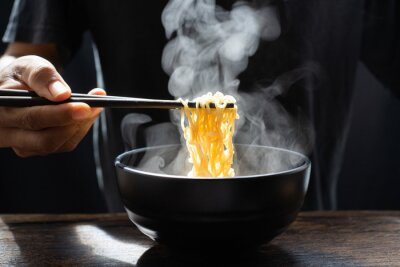 Fototapet Hand uses chopsticks to pickup tasty noodles with steam and smoke in bowl on wooden background, selective focus. Asian meal on a table, hot food and junk food concept