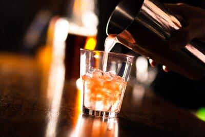 Fototapet Händerna på en bartender hälla en drink i ett glas
