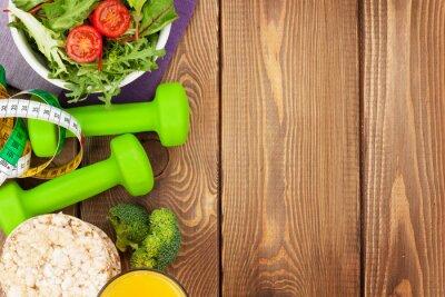 Fototapet Hantlar, måttband och hälsosam mat över träbord