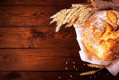 Fototapet Hemlagad bröd på trä bakgrund. Lantlig stil. Mat bakning bakgrund
