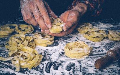 Fototapet Homemade uncooked pasta on black background. Making fresh italian fettuccine.