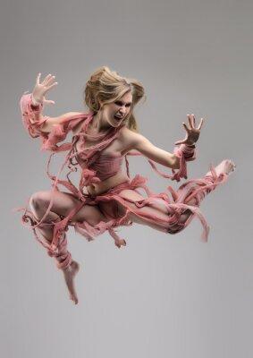 Fototapet Hoppa swathed kvinna i studio under grå bakgrund