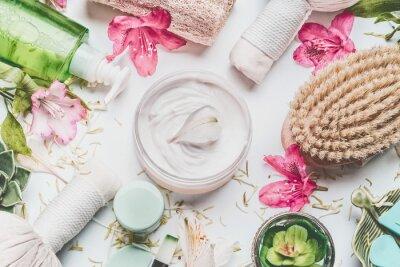 Fototapet Hudkräm med blomblad och andra kroppsvård kosmetiska produkter och tillbehör på vit bakgrund, ovanifrån