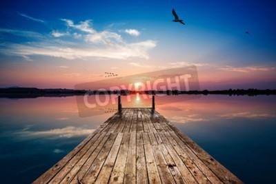 Fototapet I perspektiv av en träbrygga på dammen vid solnedgången med perfekt spegelreflektion