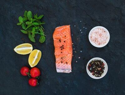 Fototapet Ingredienser. Rå lax filet, citron, körsbärstomater, färsk mynta och kryddor över mörk sten bakgrund