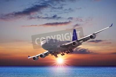 Fototapet Jet liner över havet i skymningen