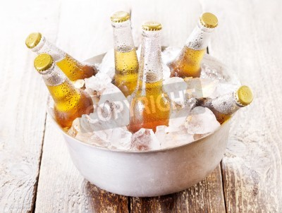 Fototapet kalla flaskor öl i hinken med is på träbord