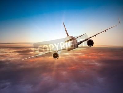 Fototapet Kommersiella flygplan flyger över moln i dramatisk solnedgång ljus