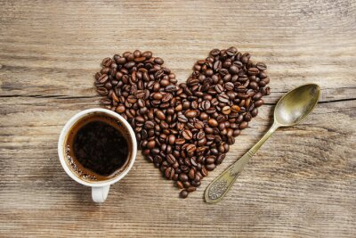 Fototapet Kopp kaffe och hjärta av kaffebönor på träbord. Till