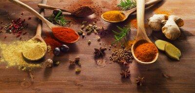 Fototapet Kryddor och örter på träbord.