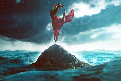 Fototapet Kvinna dansar på en klippa i havet