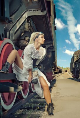 Fototapet Kvinna i vintageklänning sitter på lokets hjul.