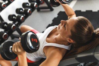Fototapet Kvinna lyft vikter och arbetar på hennes bröst på gymmet