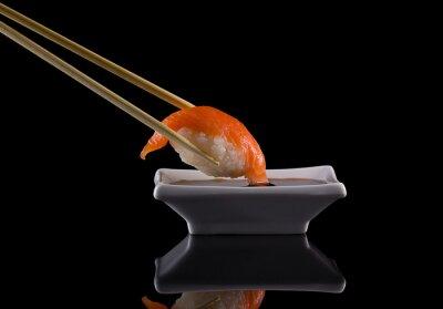 Fototapet Lax sushi nigiri i pinnar med sojasås över svart bakgrund