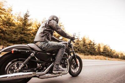 Fototapet Man säte på motorcykeln på vägen i skogen.